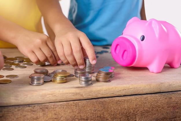 Le mani dei bambini stanno aiutando a mettere le monete nel porcellino salvadanaio