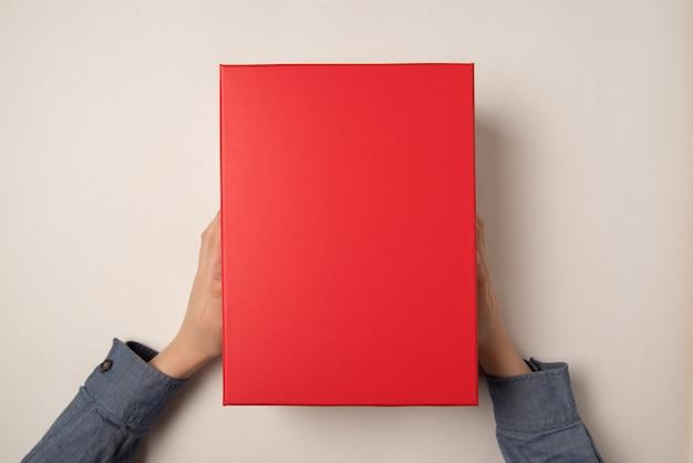 Le mani dei bambini tengono una confezione regalo rossa. sfondo bianco. vista dall'alto. copia spazio