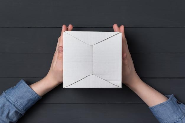 Le mani dei bambini tengono una scatola di cartone bianca. sfondo nero.