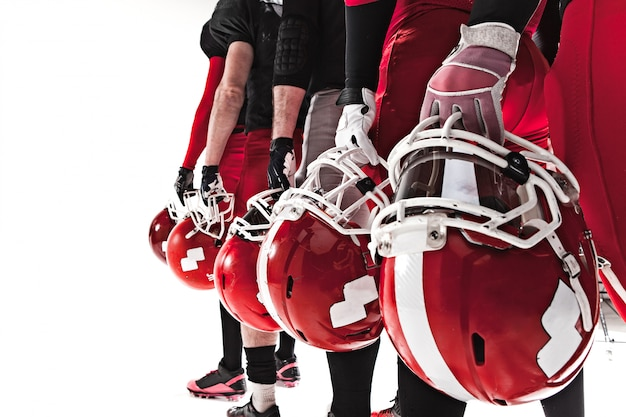 Le mani dei giocatori di football americano con i caschi su spazio bianco