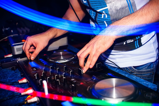 Le mani dei regolatori distorcono la musica del dj sulle apparecchiature del dj in discoteca