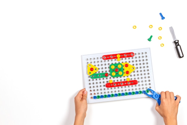 Le mani del bambino che giocano con gli strumenti variopinti dei giocattoli sulla tavola bianca. vista dall'alto