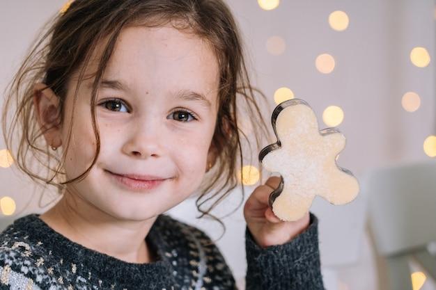 Le mani del bambino del primo piano che preparano i biscotti facendo uso delle taglierine del biscotto.