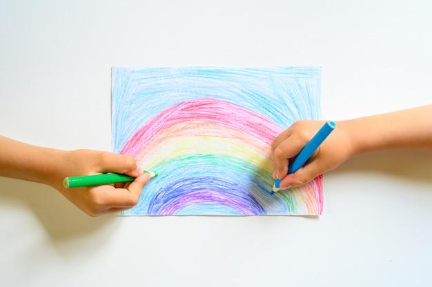 Le mani del bambino disegnano insieme le matite colorate arcobaleno su fondo bianco