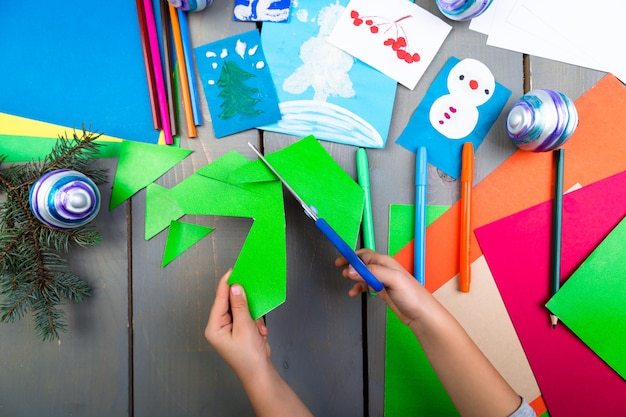 Le mani del bambino fanno giocattoli di natale fatti a mano da cartone. fai da te per bambini.