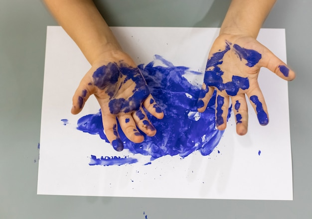 Le mani del bambino nell'arte di concetto iniziale di sviluppo della pittura blu, istruzione creativa e prescolare per il fuoco molle dei bambini