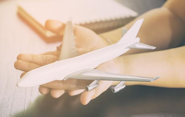 Le mani del bambino sta tenendo un giocattolo bianco dell'aeroplano per il concetto di viaggio di chidlren
