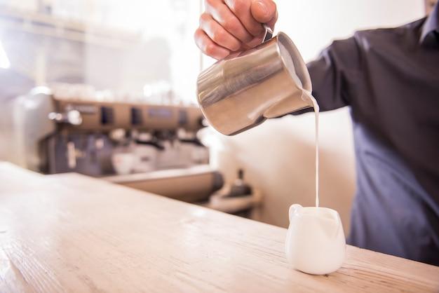 Le mani del barista stanno versando il latte facendo cappuccino.