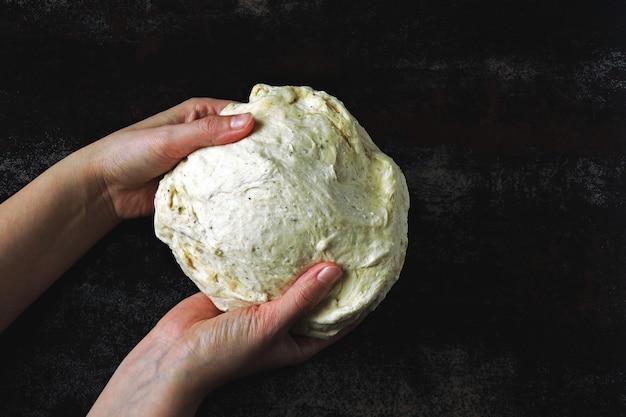 Le mani del cuoco tengono e impastano la pasta. pasta lievitata su una superficie scura. pasta cruda per cottura.