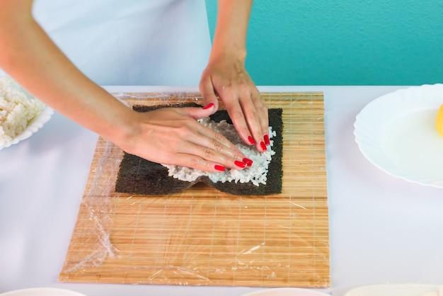 Le mani del cuoco unico della donna che riempiono i rotoli di sushi giapponesi con riso su uno strato dell'alga di nori.