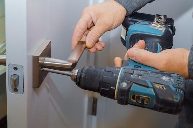 Le mani del falegname della porta interna bloccate dell'installazione installano la serratura