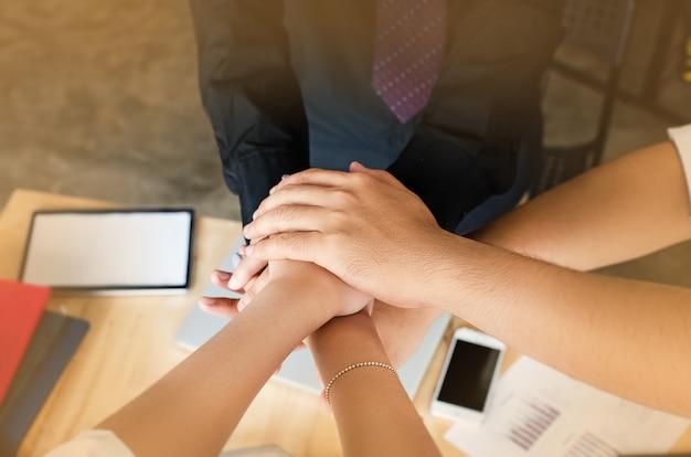 Le mani del gruppo aziendale accatastate insieme, unendo i concetti di lavoro di squadra