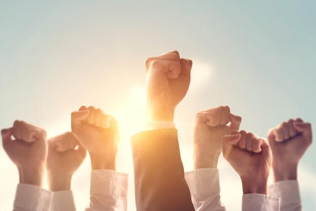 Le mani del gruppo di affari hanno sollevato l'aria del pugno vittoria corporativa di celebrazione, successo e concetto di conquista.
