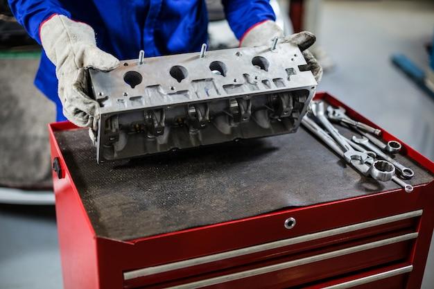 Le mani del meccanico controllo parti di automobili