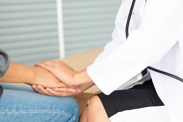 Le mani del medico femminile amichevole che tengono la mano del paziente femminile per incoraggiamento ed empatia