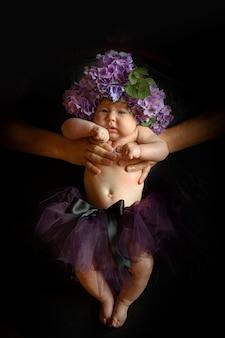 Le mani del padre tengono in mano una figlioletta con fiori di ortensia in testa. girato in una stanza nera.