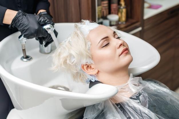 Le mani del parrucchiere stanno lavando i capelli di una donna in un lavandino dopo la colorazione dei capelli.