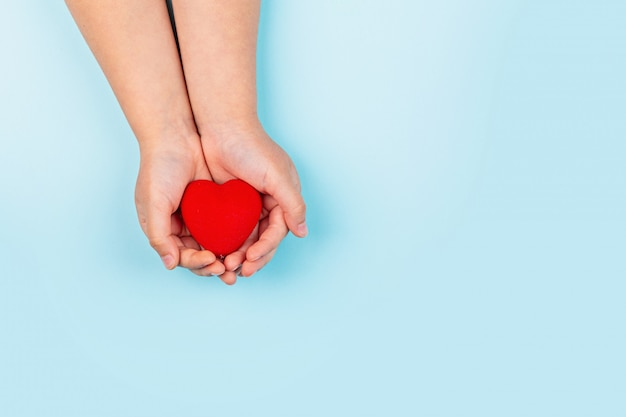 Le mani del piccolo bambino che tengono cuore rosso
