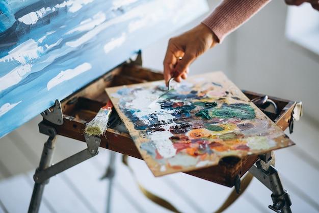 Le mani del pittore si chiudono su che mescolano le vernici