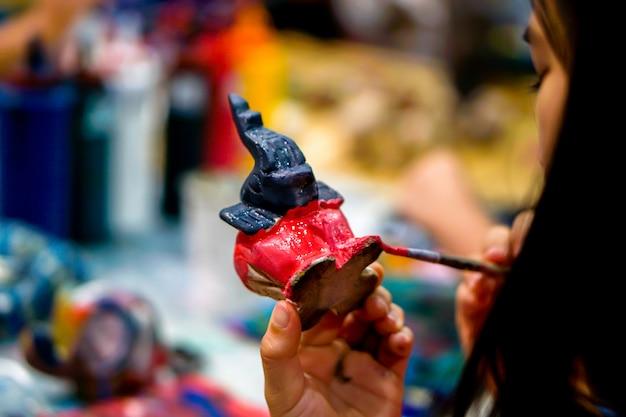 Le mani del primo piano degli studenti d'arte che tengono il pennello studiano e imparano la pittura sulla bambola animale di legno nell'aula di arte.