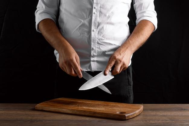 Le mani del primo piano del cuoco unico affilano un coltello da cucina su un coltello