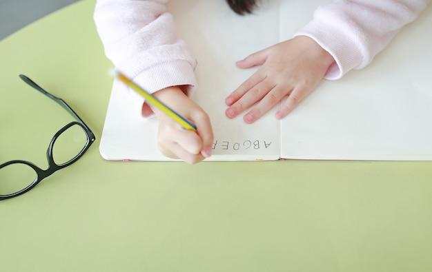 Le mani del primo piano di piccolo bambino scrive l'abc in un libro o in un taccuino con la matita sulla tavola.