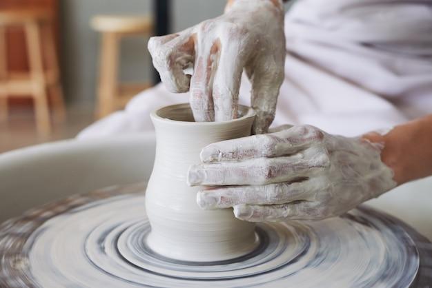 Le mani del vasaio femminile che fa il vaso dell'argilla sulla filatura spingono dentro l'officina