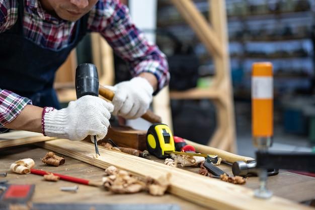 Le mani dell'artigiano intagliano con una sgorbia