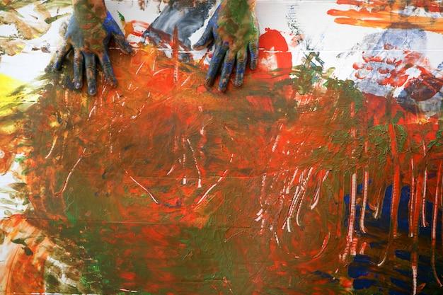 Le mani dell'artista dei bambini che dipingono i multi colori