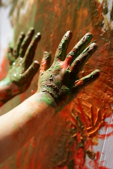 Le mani dell'artista dei bambini che dipingono variopinto