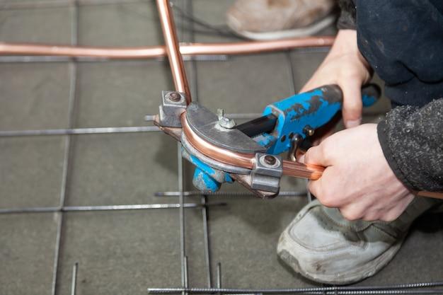 Le mani dell'idraulico piegano i tubi di rame per curvatubi
