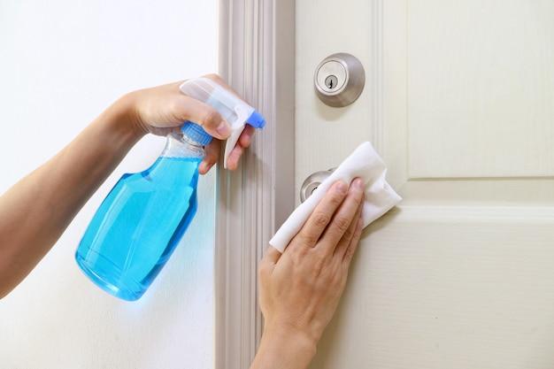 Le mani dell'uomo che tengono la bottiglia del pulitore dell'alcool per la maniglia della porta della stanza di pulizia