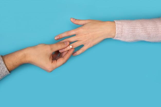 Le mani dell'uomo che tengono la fede nuziale nel dito della mano della donna sul blu.