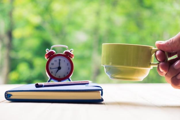 Le mani dell'uomo che tengono una tazza di caffè con il taccuino, la penna e la sveglia su un desktop dalla plancia di legno nello sfondo naturale.