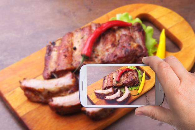 Le mani dell'uomo con lo smartphone che prende la foto ha grigliato le costole arrostite col barbecue con le foglie della lattuga