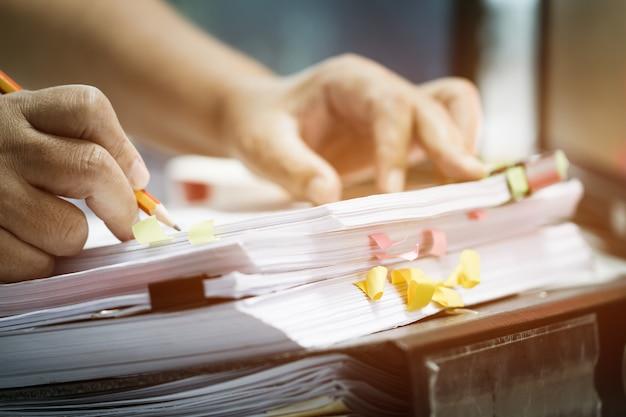 Le mani dell'uomo d'affari che tengono la matita che funziona nelle pile di archivi cartacei che cercano i documenti non finiti raggiunge