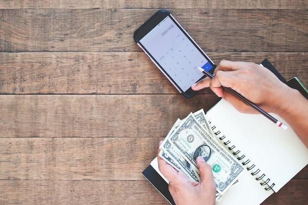 Le mani dell'uomo di vista superiore che tengono le banconote in dollari degli stati uniti e che calcolano sul telefono cellulare