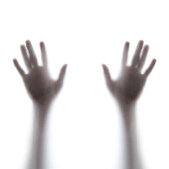Le mani dell'uomo dietro un vetro smerigliato