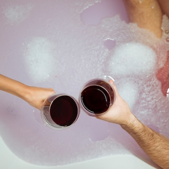 Le mani dell'uomo e della donna con i vetri della bevanda si avvicinano all'acqua con schiuma