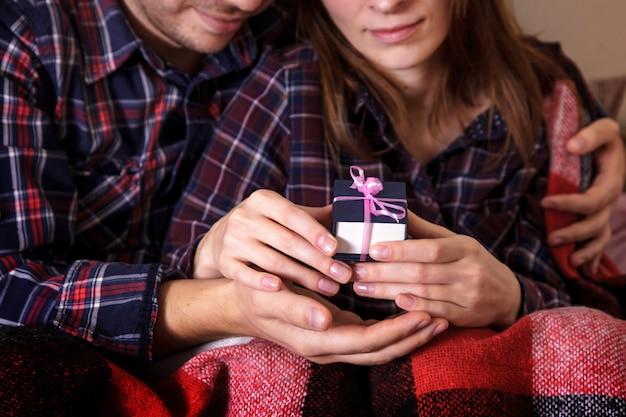 Le mani dell'uomo e della donna mantengono la confezione regalo in un plaid a forma di verme.