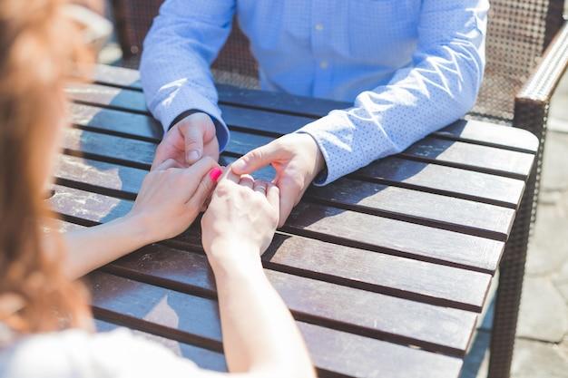 Le mani dell'uomo e della donna si sono collegate sulla tavola.