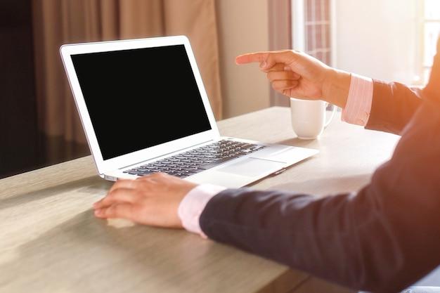 Le mani dell'uomo facendo uso del computer portatile con lo schermo in bianco sullo scrittorio nell'interno domestico.