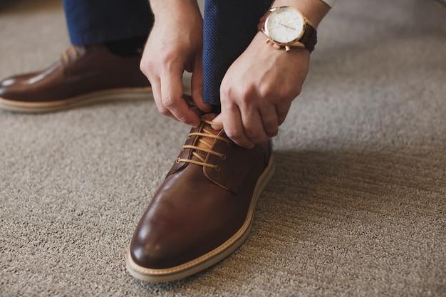 Le mani dell'uomo legano i lacci delle sue nuove scarpe