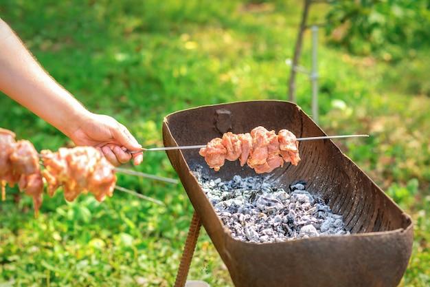 Le mani dell'uomo prepara la carne del barbecue