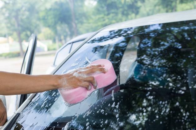 Le mani dell'uomo tengono la spugna per lavare l'automobile bianca
