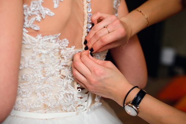 Le mani della damigella d'onore fissano i bottoni sul retro della sposa