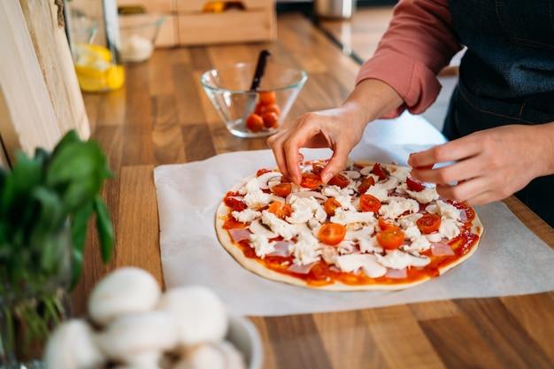 Le mani della donna che aggiungono i pomodori ciliegia ad una pizza tradizionale della margarita