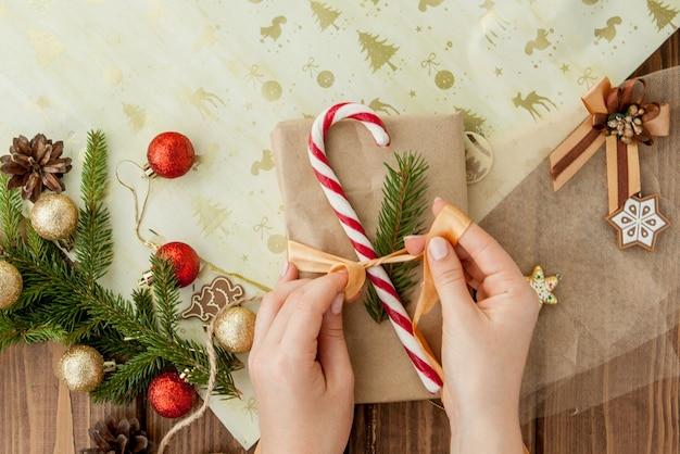 Le mani della donna che avvolgono il regalo di natale, fine su. regali di natale non preparati su legno con elementi di decorazione e oggetti, vista dall'alto. imballaggio fai-da-te di natale o capodanno.