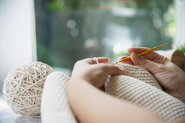 Le mani della donna che fanno il lavoro a maglia domestico