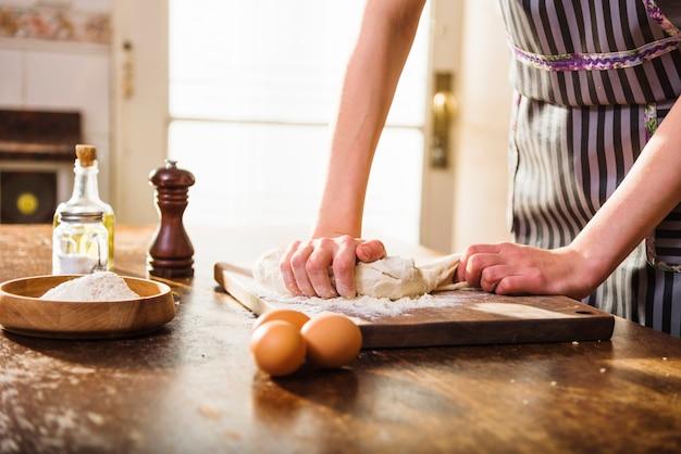 Le mani della donna che impastano la pasta con gli ingredienti di cottura sulla tavola di legno